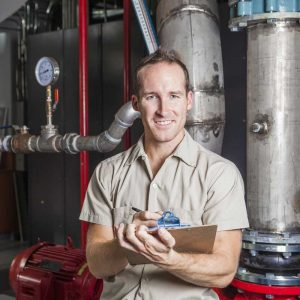 technician standing in front of a boiler